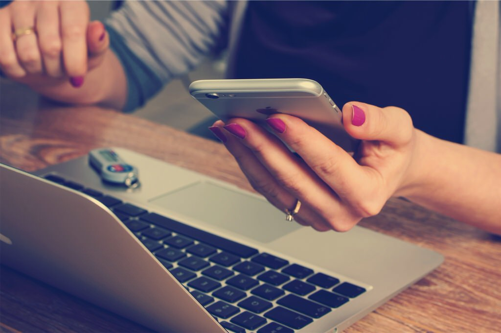 woman hands iPhone 6 MacBook Air two-factor token on wooden table