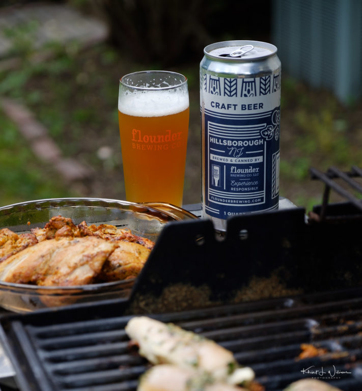 Beer in glass with chicken on grill