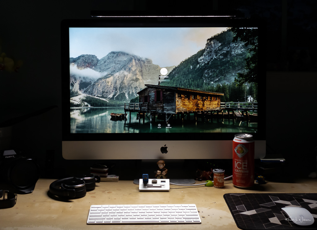 Workstation desk with iMac and other items.