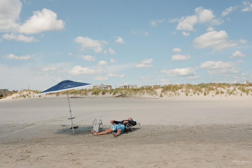 Man sleeping under umbrella Beach Scene