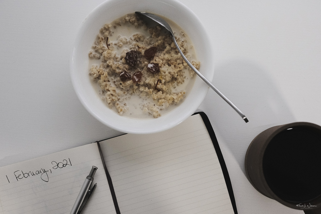 food in bowl with coffee mug and notebook