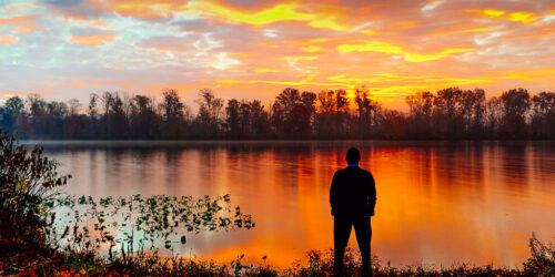 silhouette of man standing at sunrise